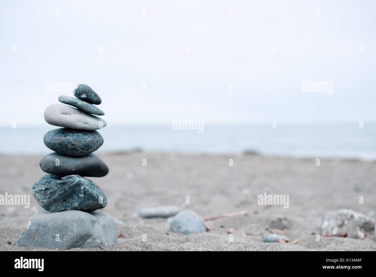 Monochrom, ruhigen, blauen gestapelte Steine auf einem Kalifornischen Strand als Symbol für Frieden, Gleichgewicht, Meditation und Achtsamkeit Stockbild