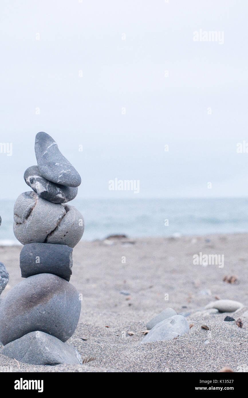 Monochrom, ruhigen, blauen gestapelte Steine auf einem Kalifornischen Strand als Symbol für Frieden, Gleichgewicht, Stockfoto
