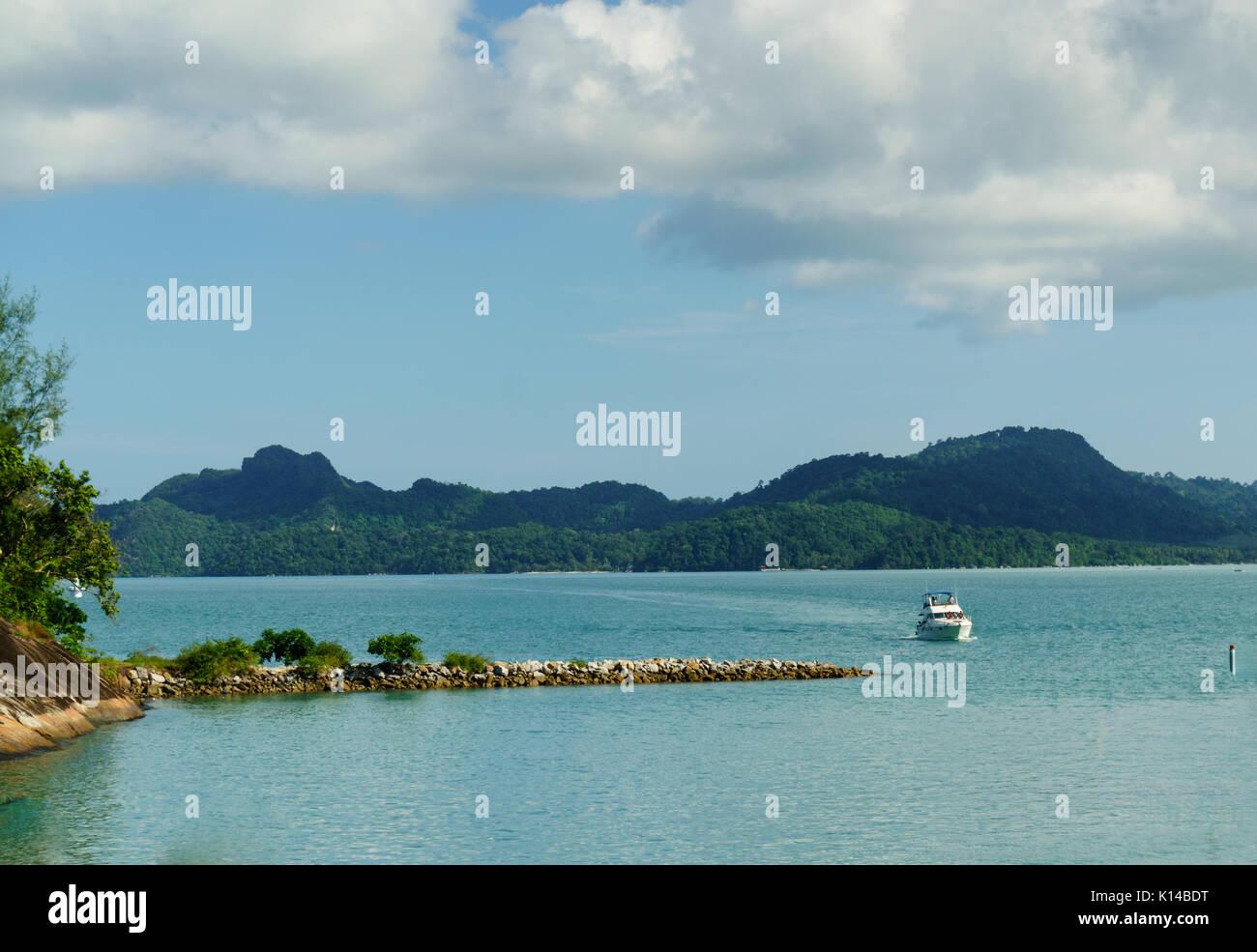 Boot nähern Felsvorsprung mit blauem Wasser und Hügel in der Stockbild