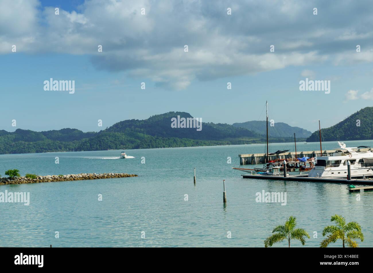 Boote auf einem Pier mit blauem Wasser und bewölkter Himmel Stockbild