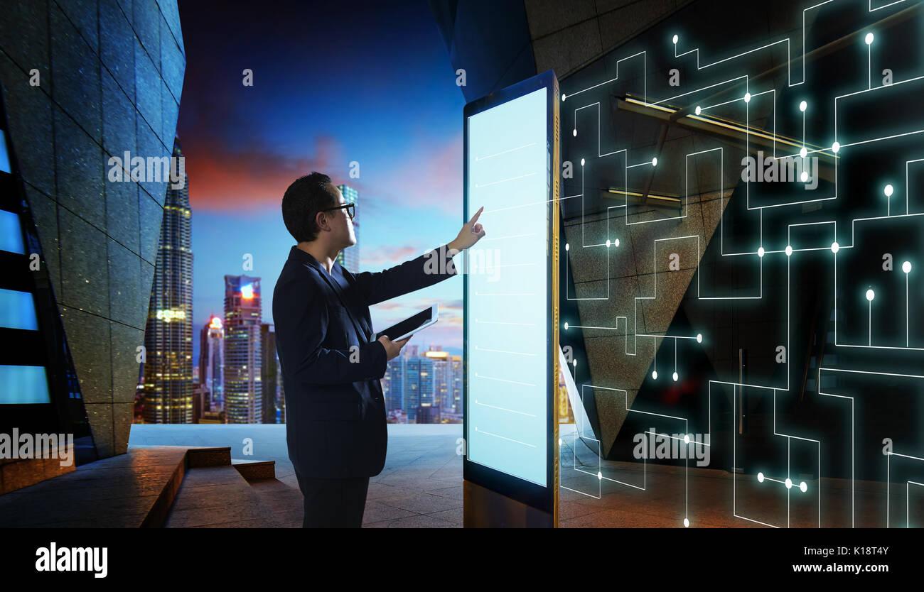 Intelligente Geschäftsmann berühren Sie den Bildschirm, die Informationen des intelligenten Kommunikationsnetz von Dingen zu suchen. Nachtaufnahme mit modernen Stadt Hintergrund Stockbild