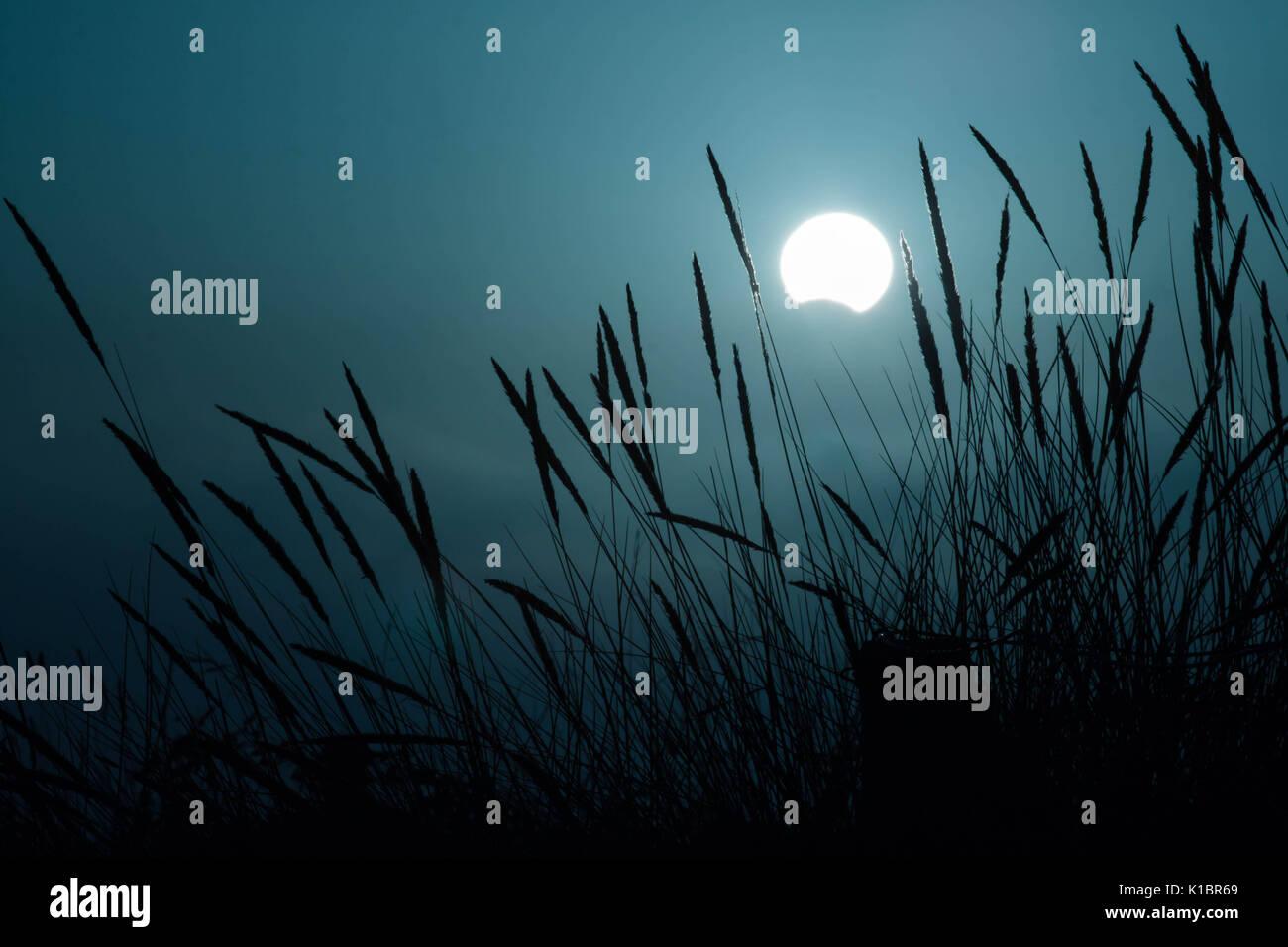 Partielle Sonnenfinsternis bei Sonnenuntergang mit Dunkelblauen Himmel Stockbild