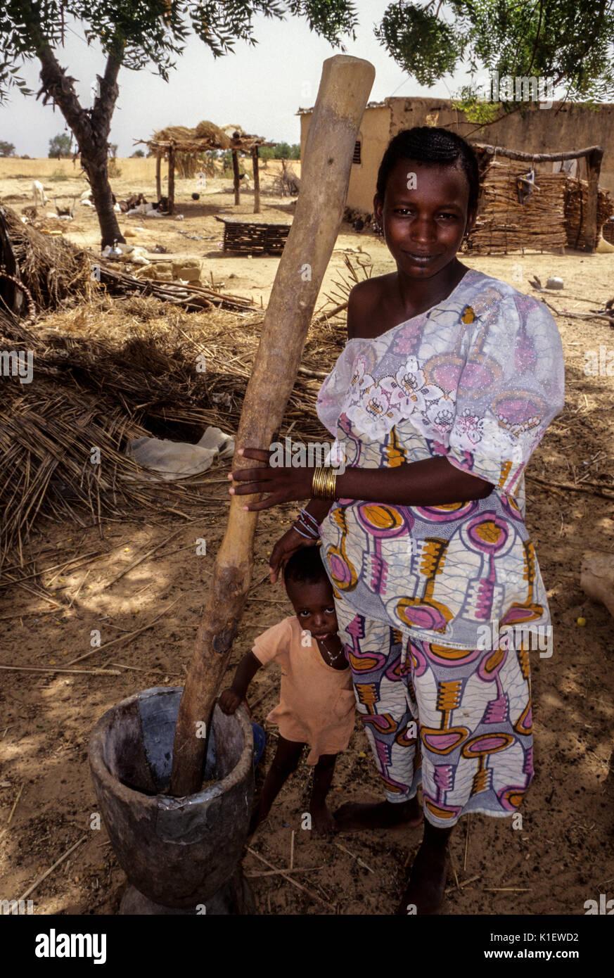Niger, Westafrika. Junge Mutter vorbereitet zu Pfund Hirse Mehl in Ihre Holz- Mörtel. Stockbild