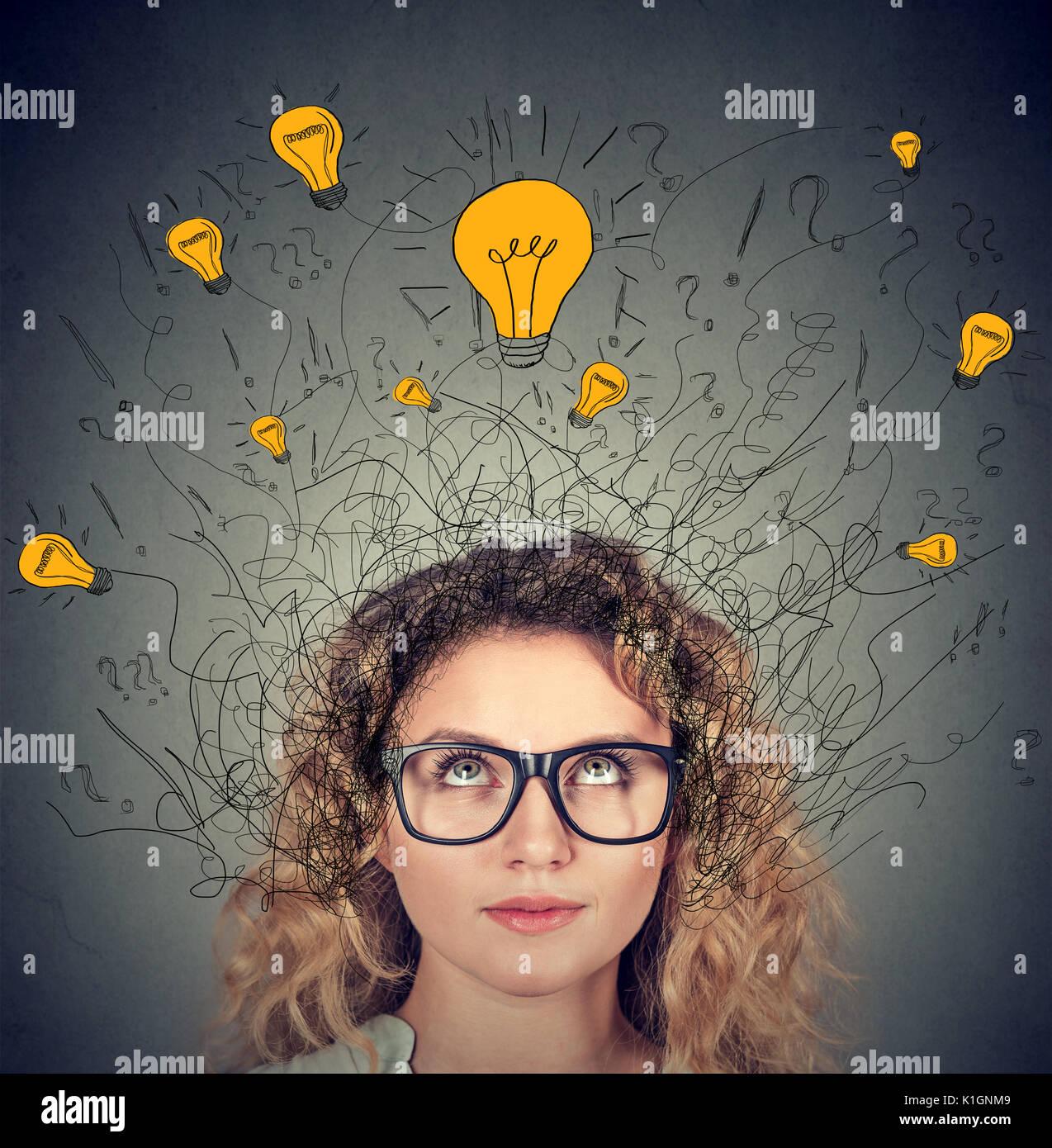 Ernsthafte Frau in Gläser mit vielen Ideen Lampen über dem Kopf suchen isoliert auf grauen Hintergrund. Eureka Kreativität Konzept Stockbild