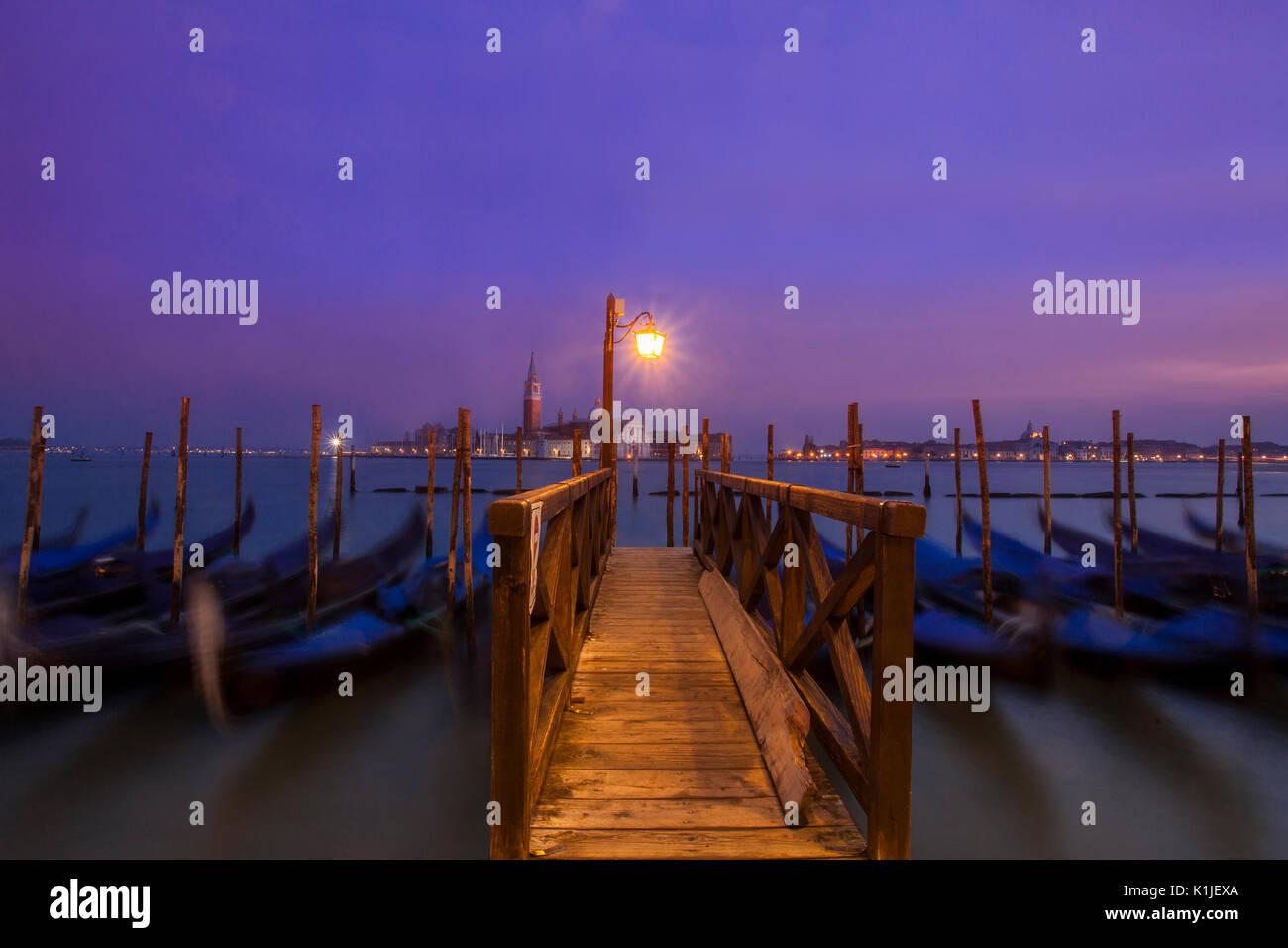 Gondeln in der Dämmerung mit der Insel San Giorgio Maggiore im Hintergrund. Stockbild
