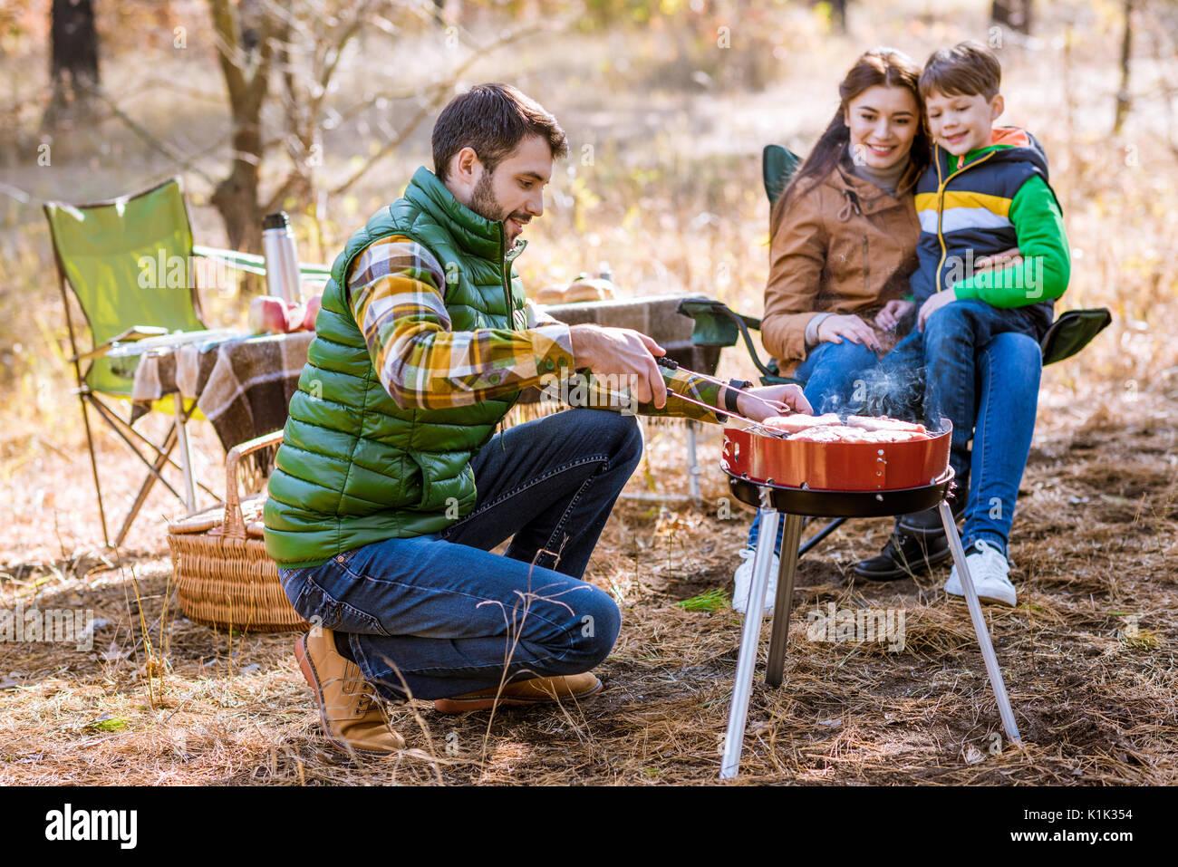 Glückliche Familie grillen von Fleisch am Grill im Herbst Park Stockbild