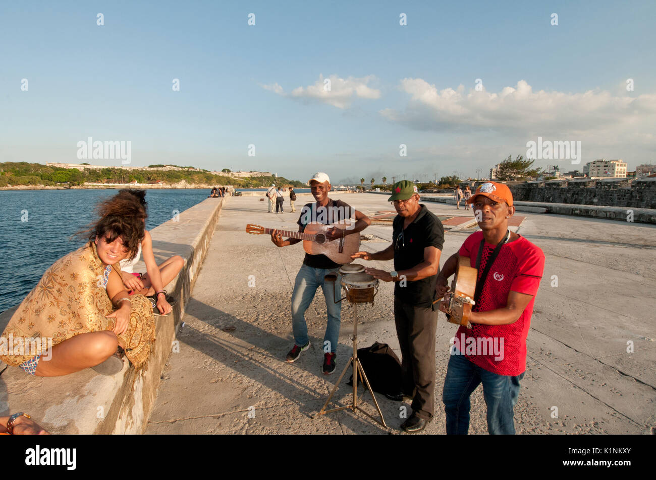 Musiker unterhalten zwei Frauen entlang der Malecon in Havanna, Kuba Stockbild