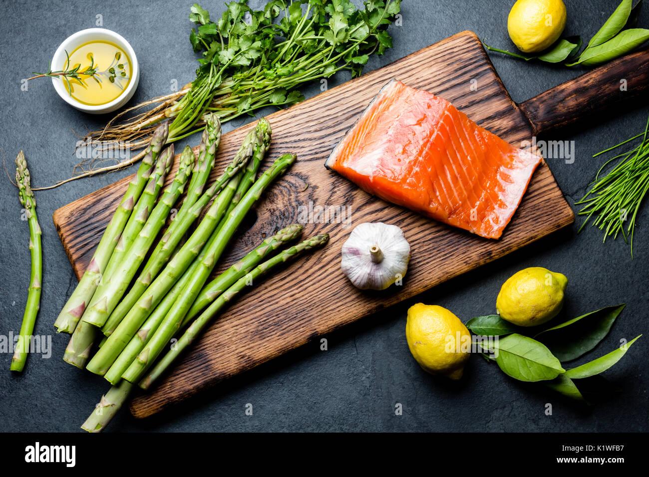 Zutaten zum Kochen. Rohes Lachsfilet, Spargel und Kräuter auf Holzbrett. Essen kochen Hintergrund mit kopieren. Ansicht von oben Stockbild