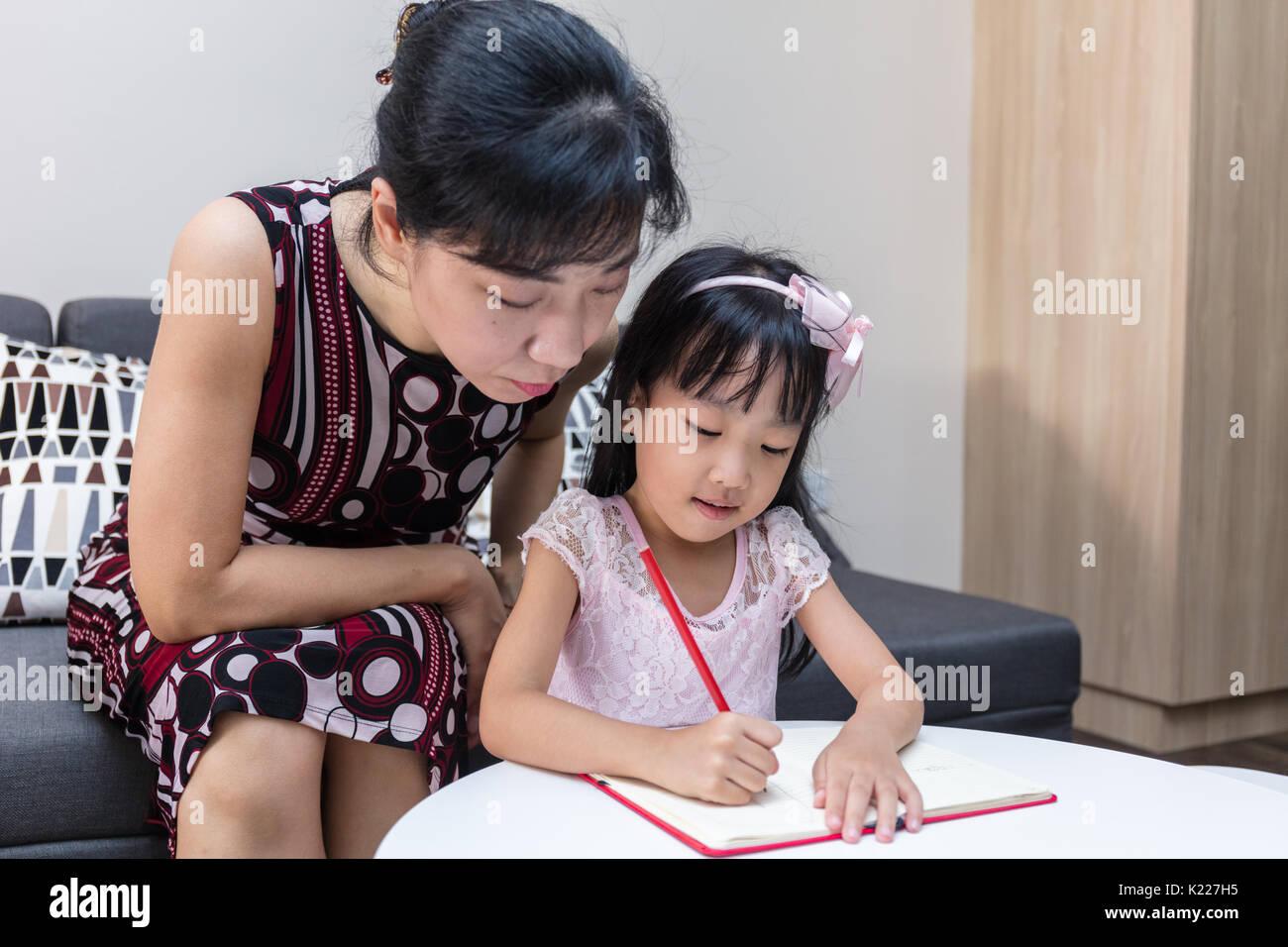 Asiatische chinesische Mutter lehre Tochter Hausaufgaben zu Hause Stockbild