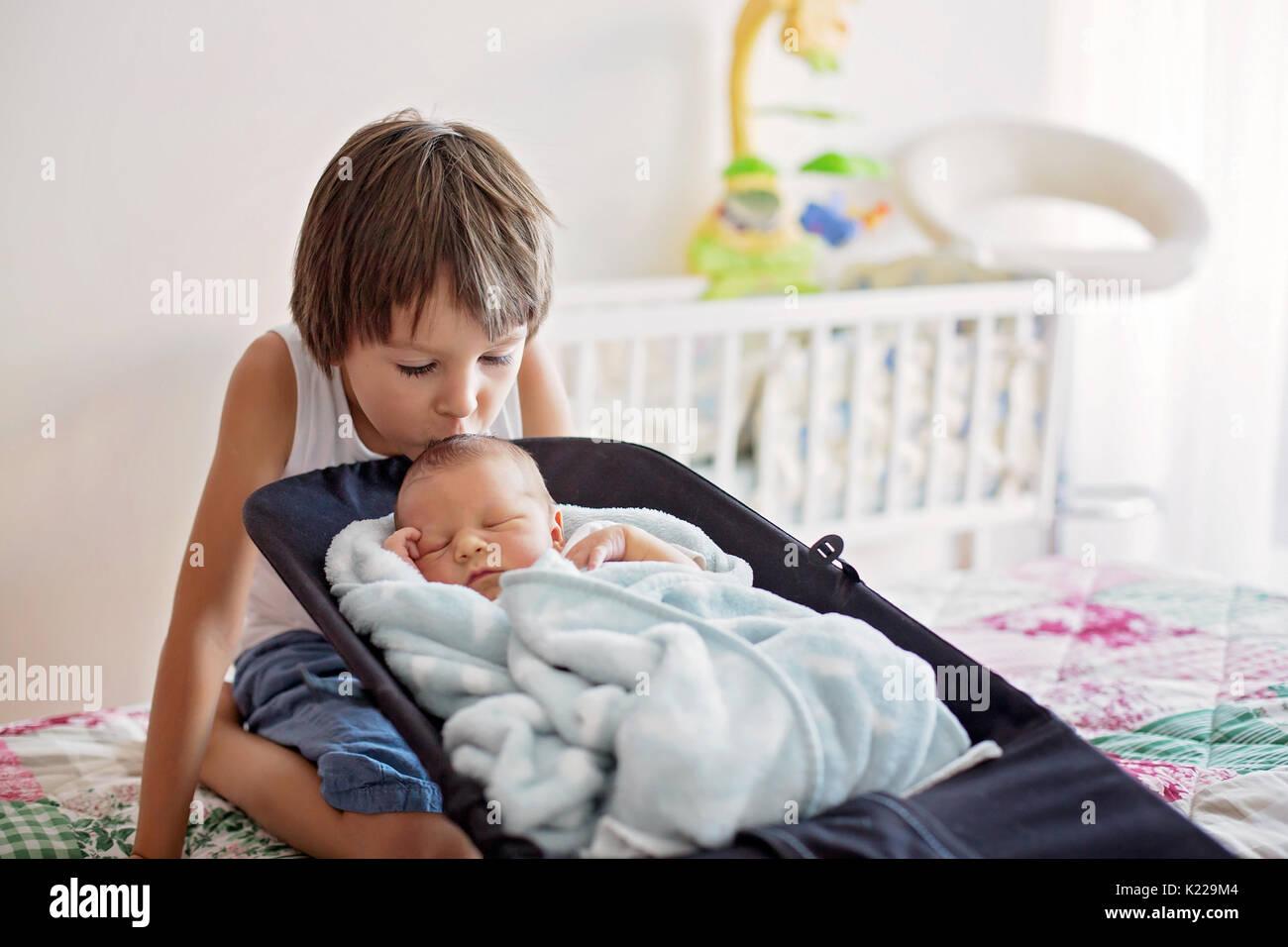 Schöne junge, umarmen mit Zärtlichkeit und sein neugeborenes Baby Bruder Pflege zu Hause. Familie Liebe Glück Konzept Stockbild