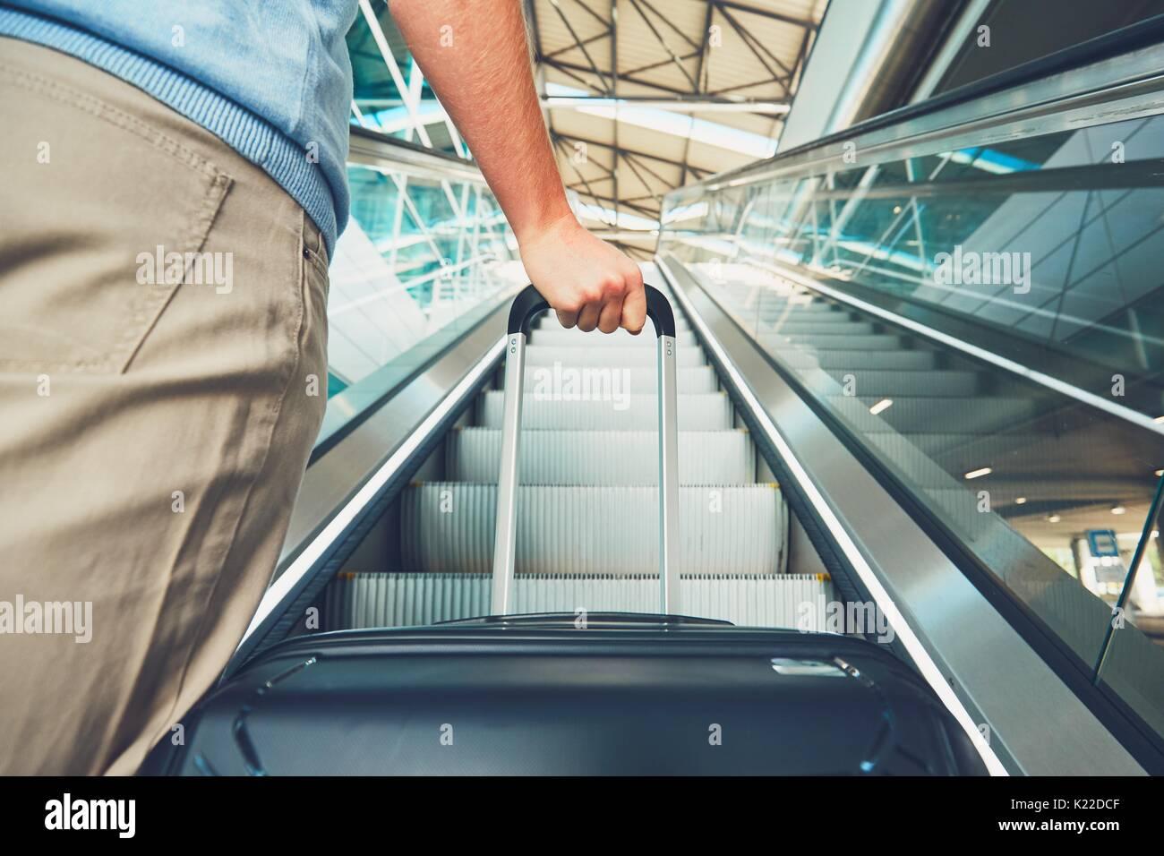 Mann mit dem Flugzeug reisen. Hand des Reisenden mit Gepäck auf der Rolltreppe am Flughafen. Stockbild
