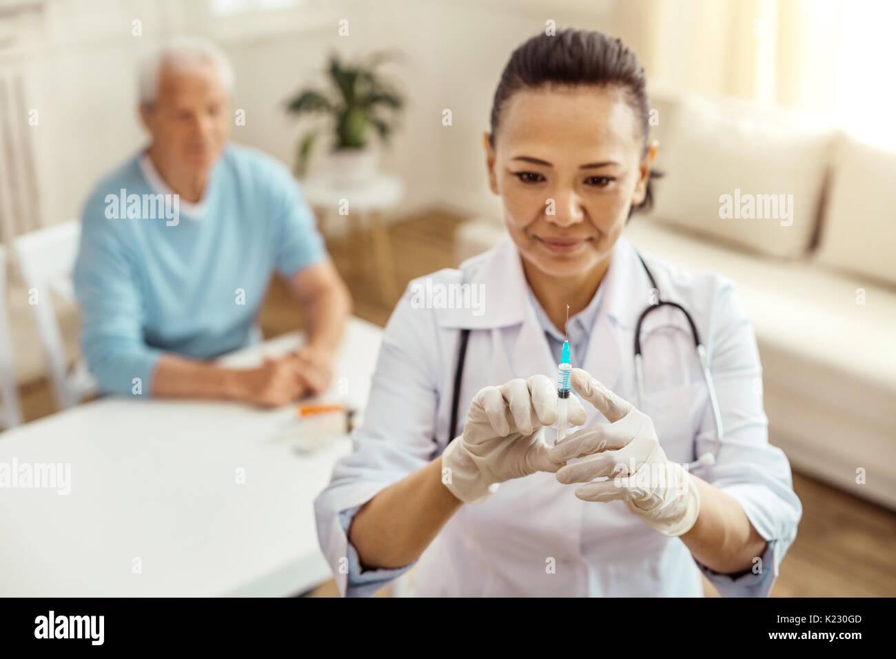 Fröhliche positive Krankenschwester Testen der Spritze Stockbild