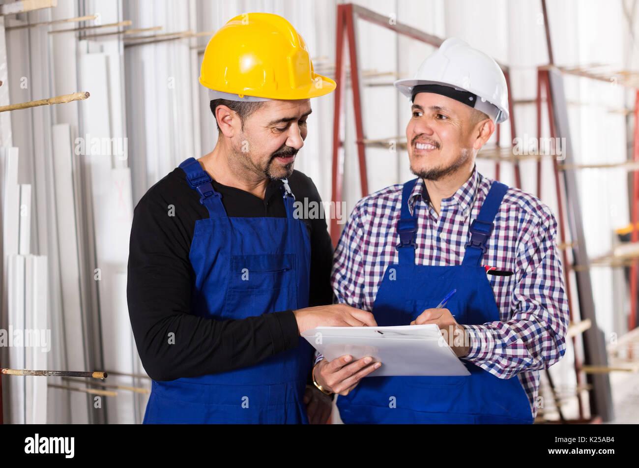 Positive Maschinenbauingenieur Überprüfung der Arbeit der Arbeit an modernen Fabrik Stockbild
