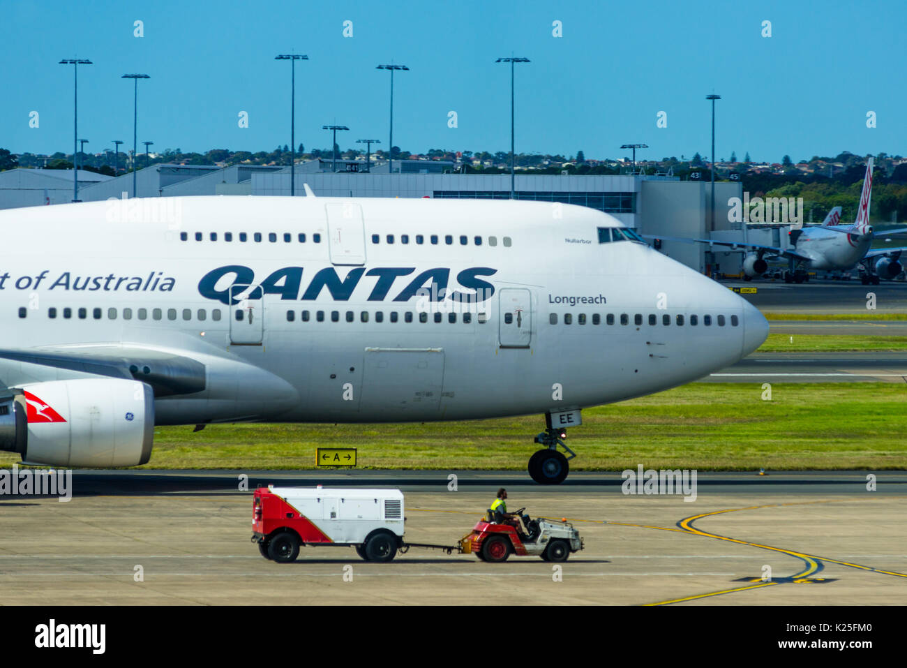 Eine Qantas 747 Jumbo Jet neben einem Gepäck Fahrzeug am internationalen Flughafen von Sydney, New South Wales, Australien. Stockbild