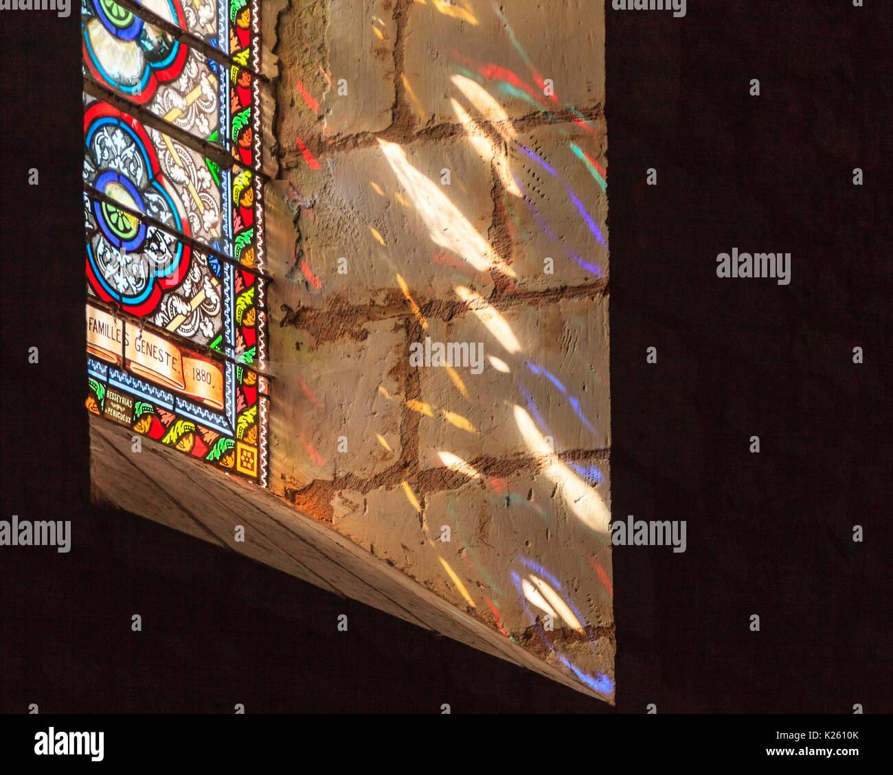 Licht, das durch ein Glasfenster im XII Jahrhundert Notre Dame de L'Himmelfahrt Kirche in Mouzens, Nouvelle Aquitaine, Frankreich Stockbild