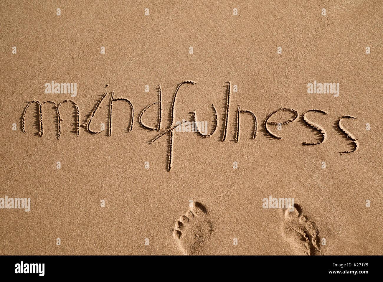 High-Angle Shot des Wortes Achtsamkeit in den Sand des Strandes geschrieben und ein paar menschliche Fußabdrücke Stockfoto