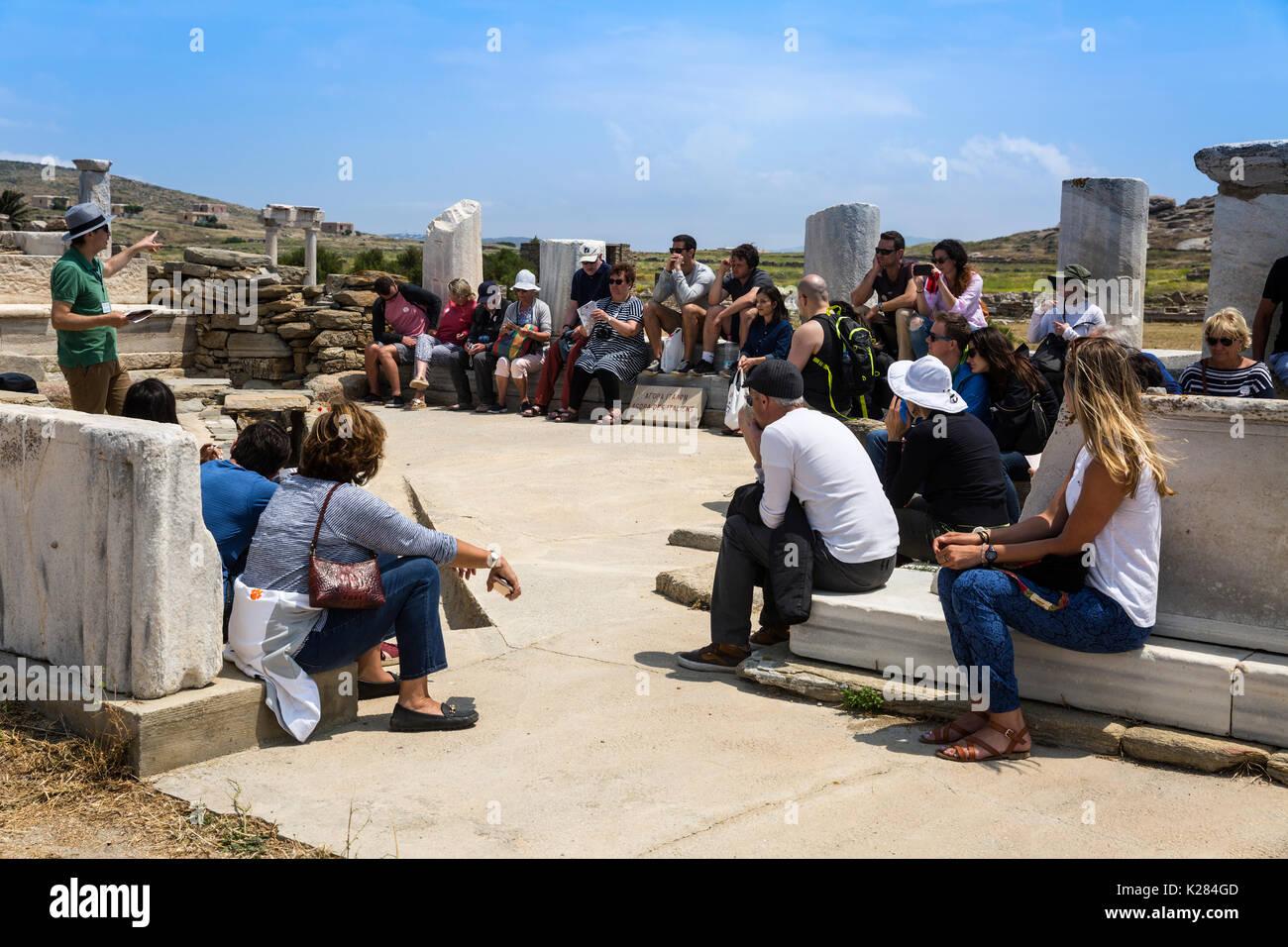 Touristen versammelt Hören zu einem Führer über die Geschichte von Delos, Kykladen, Griechenland. Stockbild