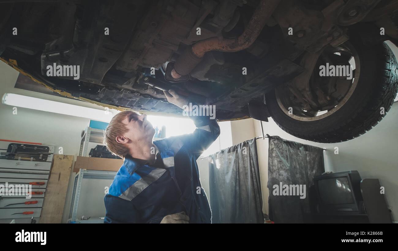 Mechanische Werkstatt - ein Mechaniker prüft die Aussetzung der Auto, Weitwinkel Stockbild