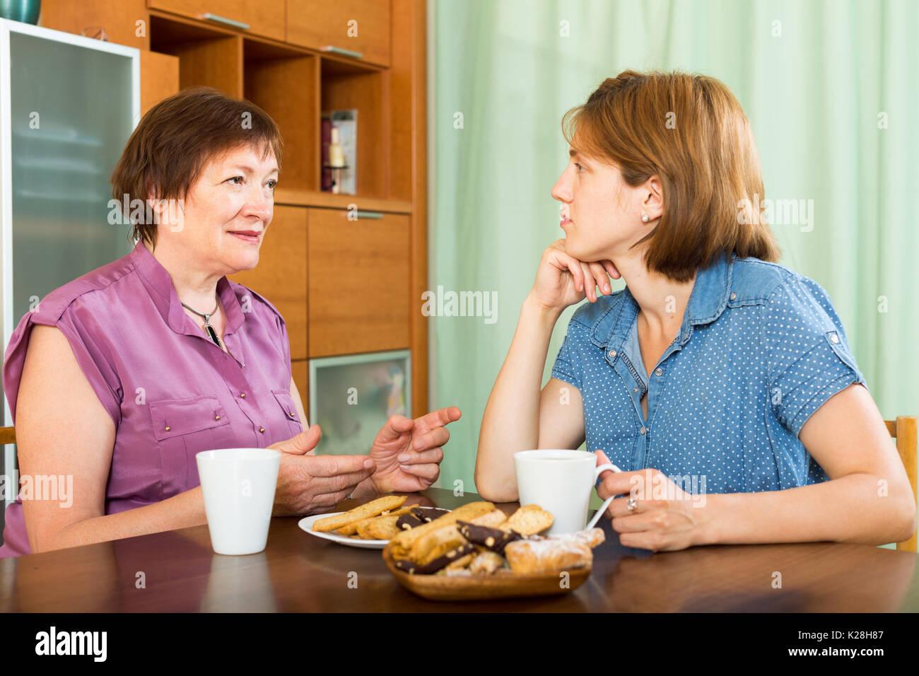 Reife Frau und ihre Tochter Tee-trinken und in einer Diskussion Stockfoto