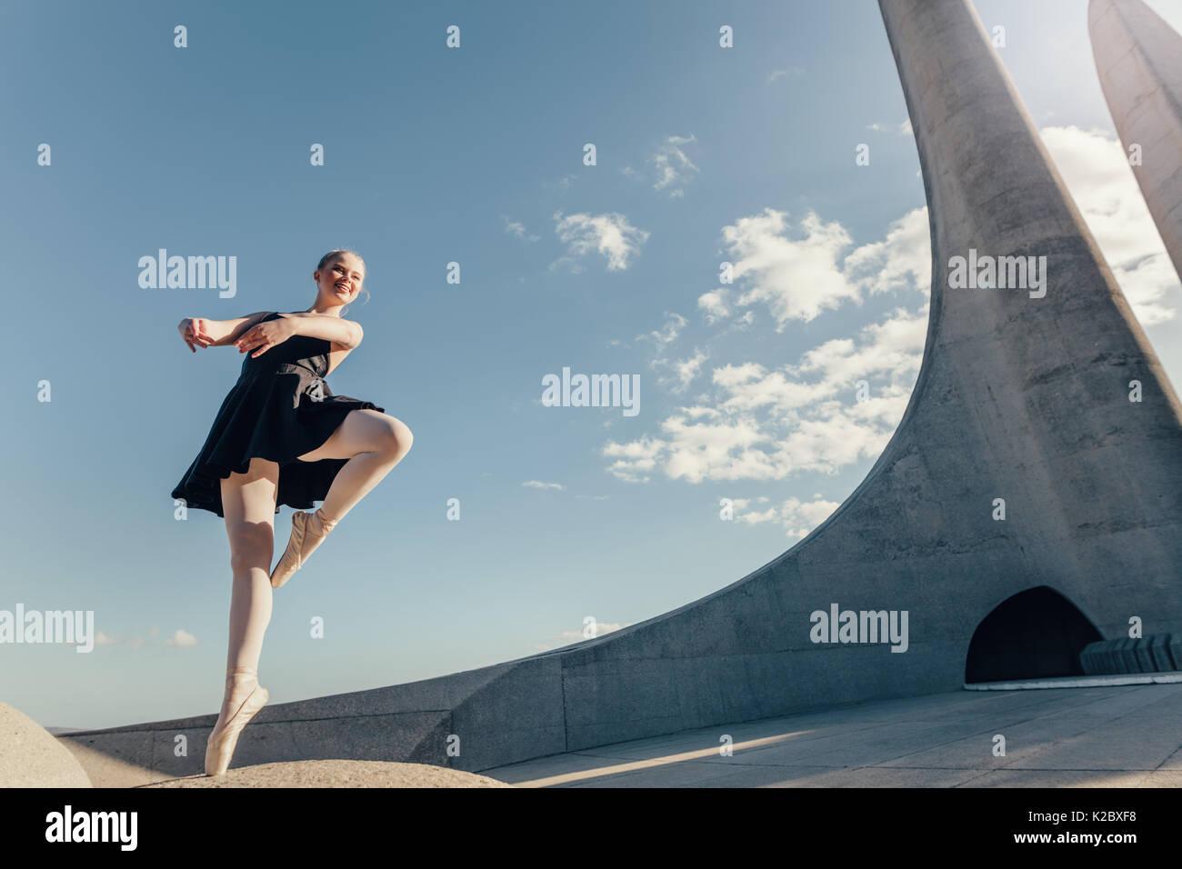 Ballet Dancer üben Tanz bewegt sich im Freien mit blauem Himmel und Denkmal  im Hintergrund. Tänzerin Balancieren auf einen Zeh in Pointe Schuhe auf  eine Ro 58ca654c9e