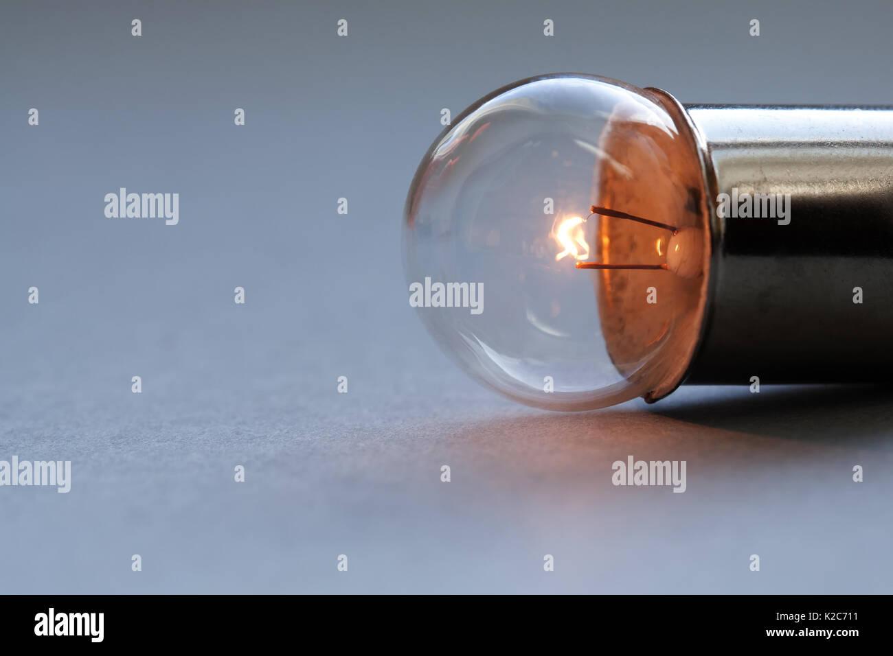 Vintage Glühbirne auf grauem Hintergrund. Glühende Heizfaden close-up. Soft Focus, kopieren Raum Stockbild