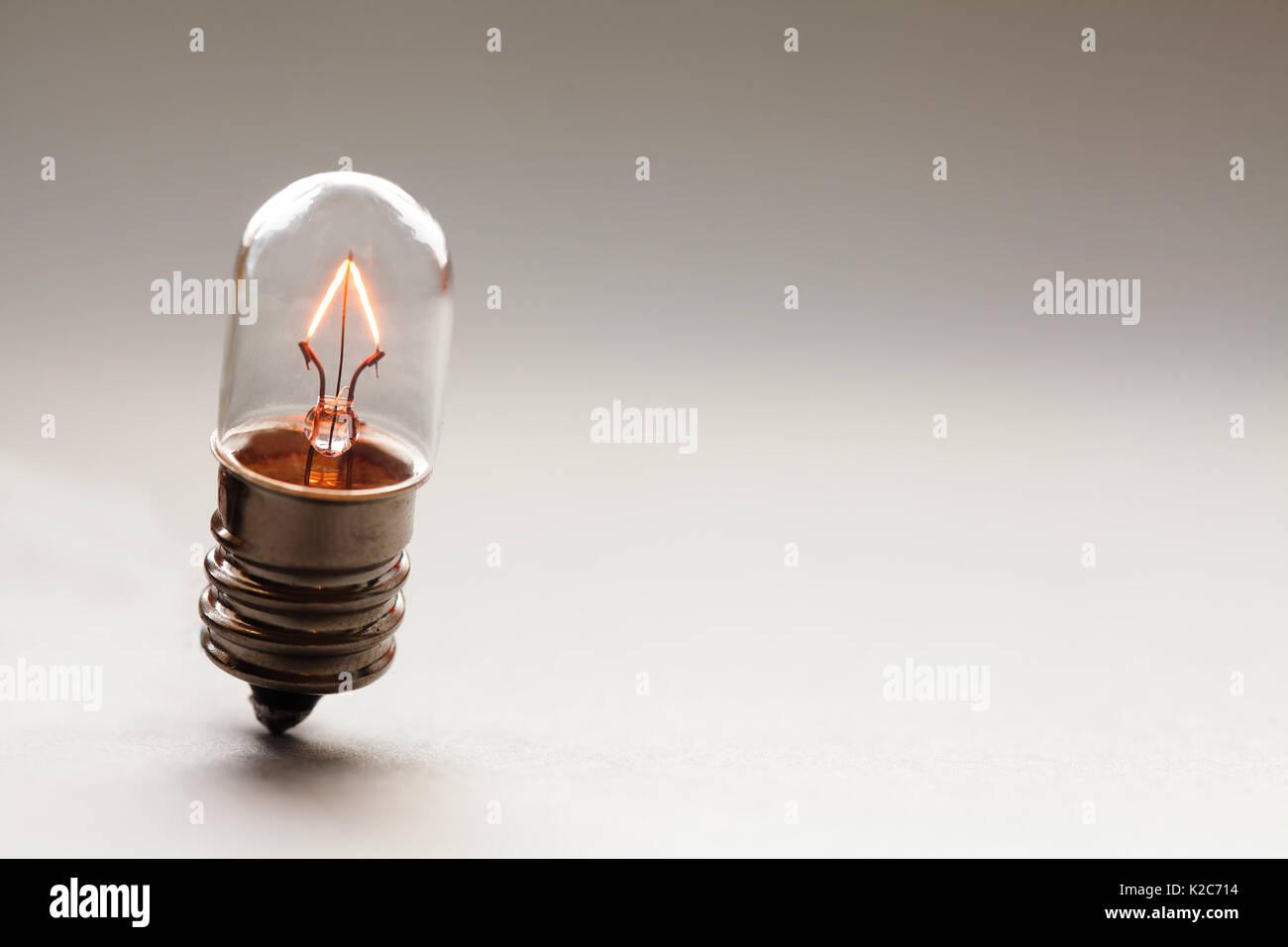 Leuchtende Glühbirne, Retro Style Glühlampe Makro anzeigen. Warme Farben gradient Hintergrund. Soft Focus. Platz kopieren Stockbild