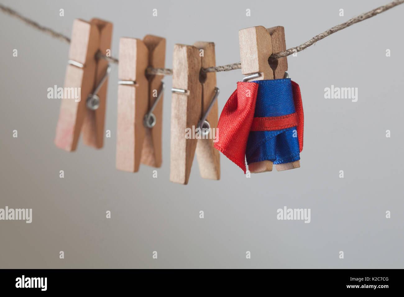 Mutigen Superhelden mit Holz Wäscheklammern team Freunde. Wäscheklammer leader Charakter in blauen Anzug roten Cape. grauen Farbverlauf Hintergrund. Soft Focus. Makro anzeigen Stockbild