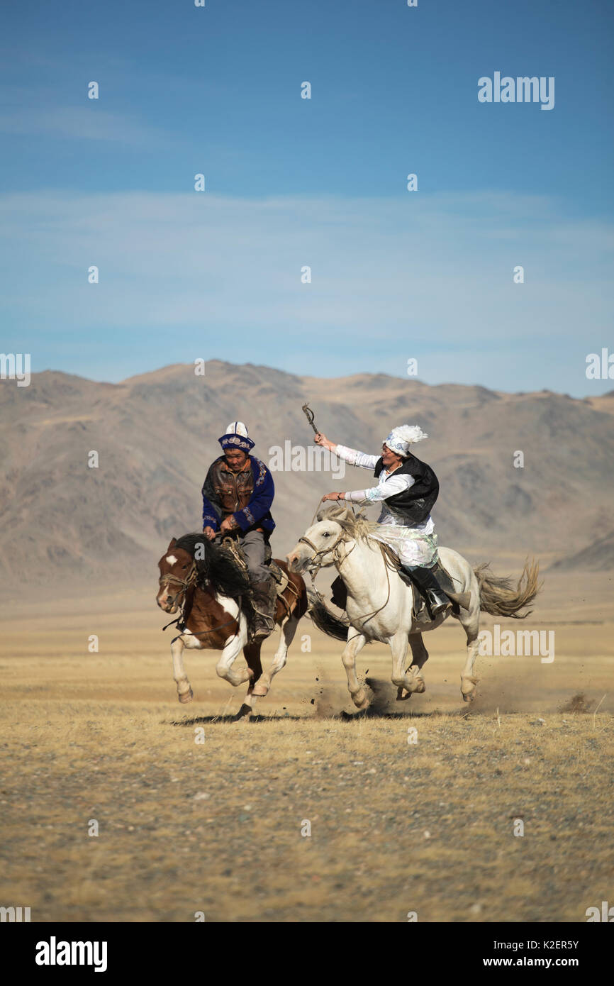 Eagle Hunter Frau spannend Mann auf langsamen Mongolische Pferd, um zu versuchen, ihn während des Spiels bei der Eagle Hunter Festival zu verlangsamen. Sie ist auf ein schnelleres Pferd, aber wenn er gewinnt das Spiel, das er zu einem Kuss berechtigt ist. Adler Jäger Festival, in der Nähe von Sagsai, Bayan-Ulgii Aymag und Mongolei. September 2014 .. Stockbild