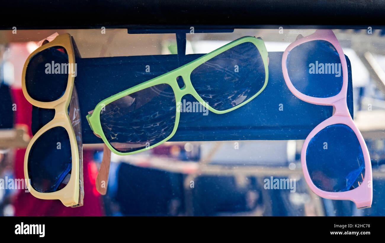 Bunte Sonnenbrille von rosa, gelb und grün Farben hängen an