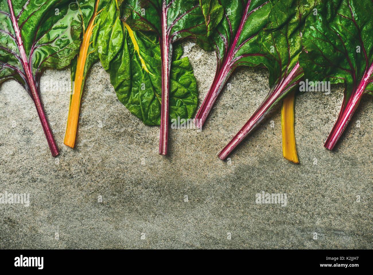 Flachbild-lay von frischen bunten Blätter Mangold über konkrete Stein, Kopieren, Ansicht von oben. Essen Rahmen. Sauber Essen, vegan, Vegetarisch, al Stockbild