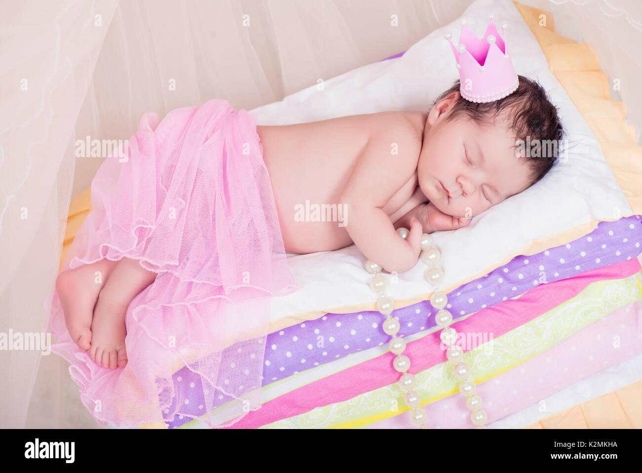 Prinzessin auf der erbse bett  Neugeborenes Mädchen in einer Krone schlafend auf dem Bett von ...
