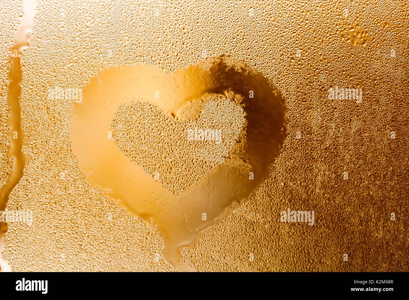 Liebe Herz Form und Regentropfen Strukturmuster. Abstrakte goldene Farbe Fenster mit Wassertropfen, Flüssigkeit blasen. Makro anzeigen. Geringe Tiefenschärfe. Valentines Tag Konzept. Horizontale Stockbild