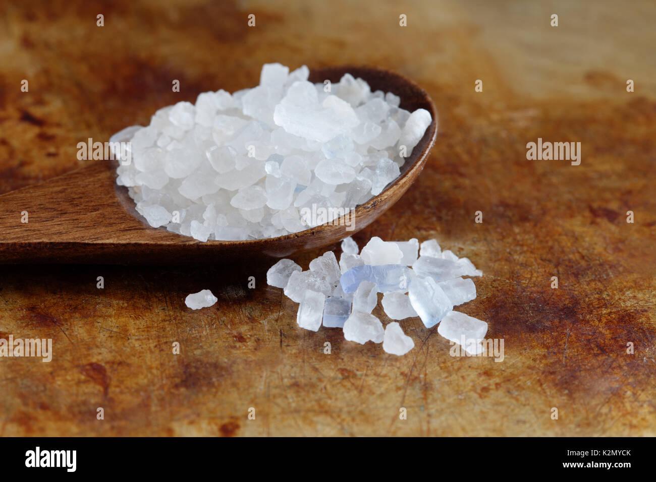 Iranische essen Persisch blau Salz crystal Makro anzeigen. Mineral Salz Natriumchlorid aus. Organische Teigwarensoße Löffel aus Holz, im Alter von Rusty Hintergrund. Geringe Tiefe Feld Stockbild