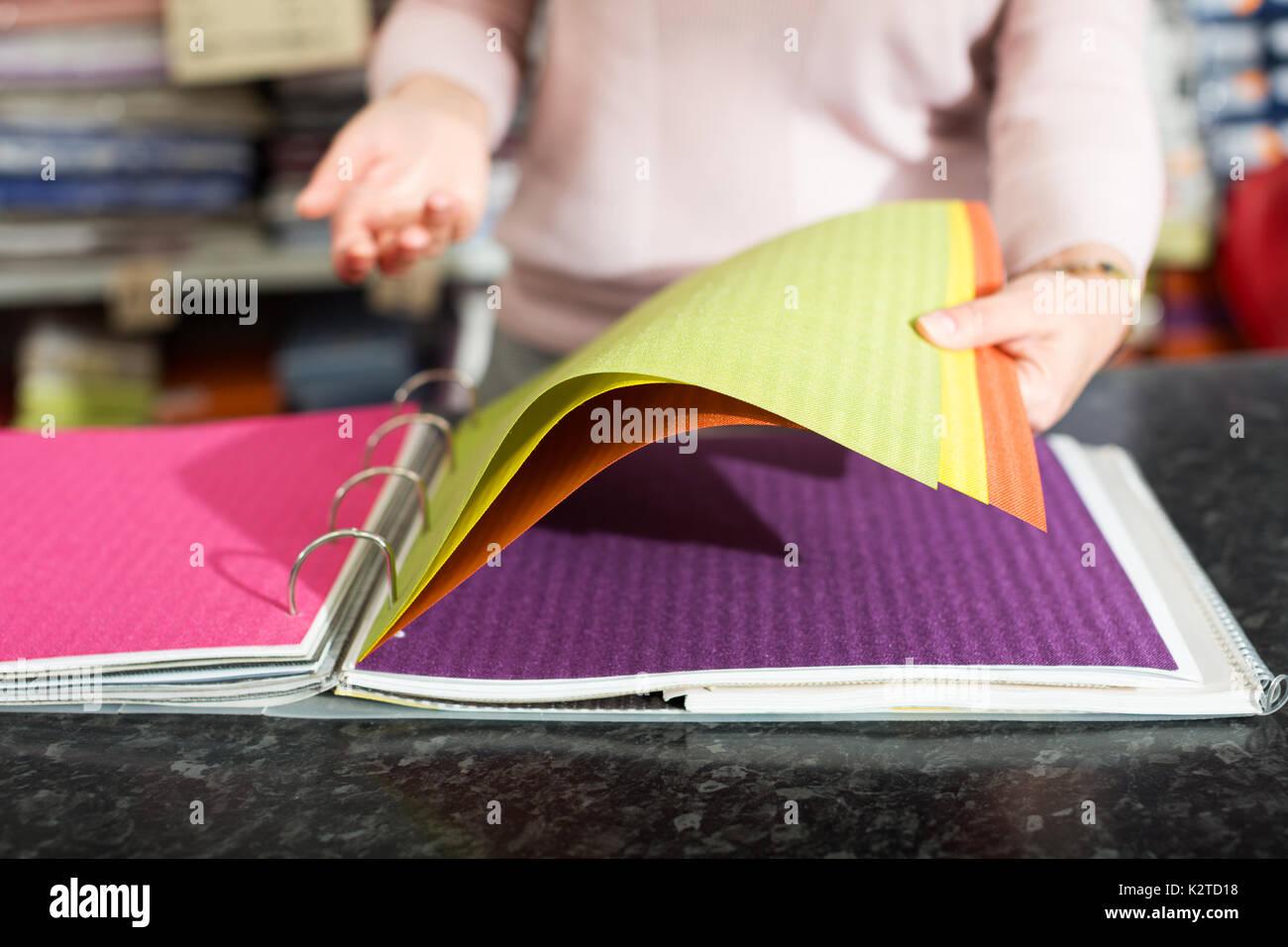 Verkäufer mit Stoff Muster Ordner im Textilgeschäft insite Stockbild