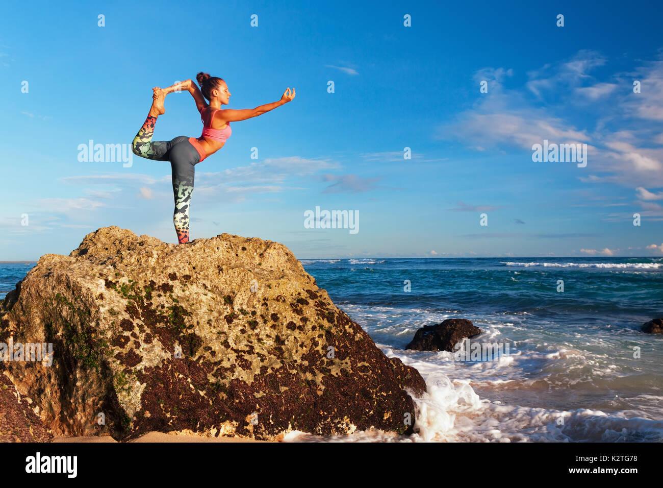 Meditation über Sonnenuntergang Himmel Hintergrund. Junge aktive Frau stand in Yoga pose am Strand Rock passen und Gesundheit zu halten. Gesunder Lebensstil, Fitness im Freien. Stockbild