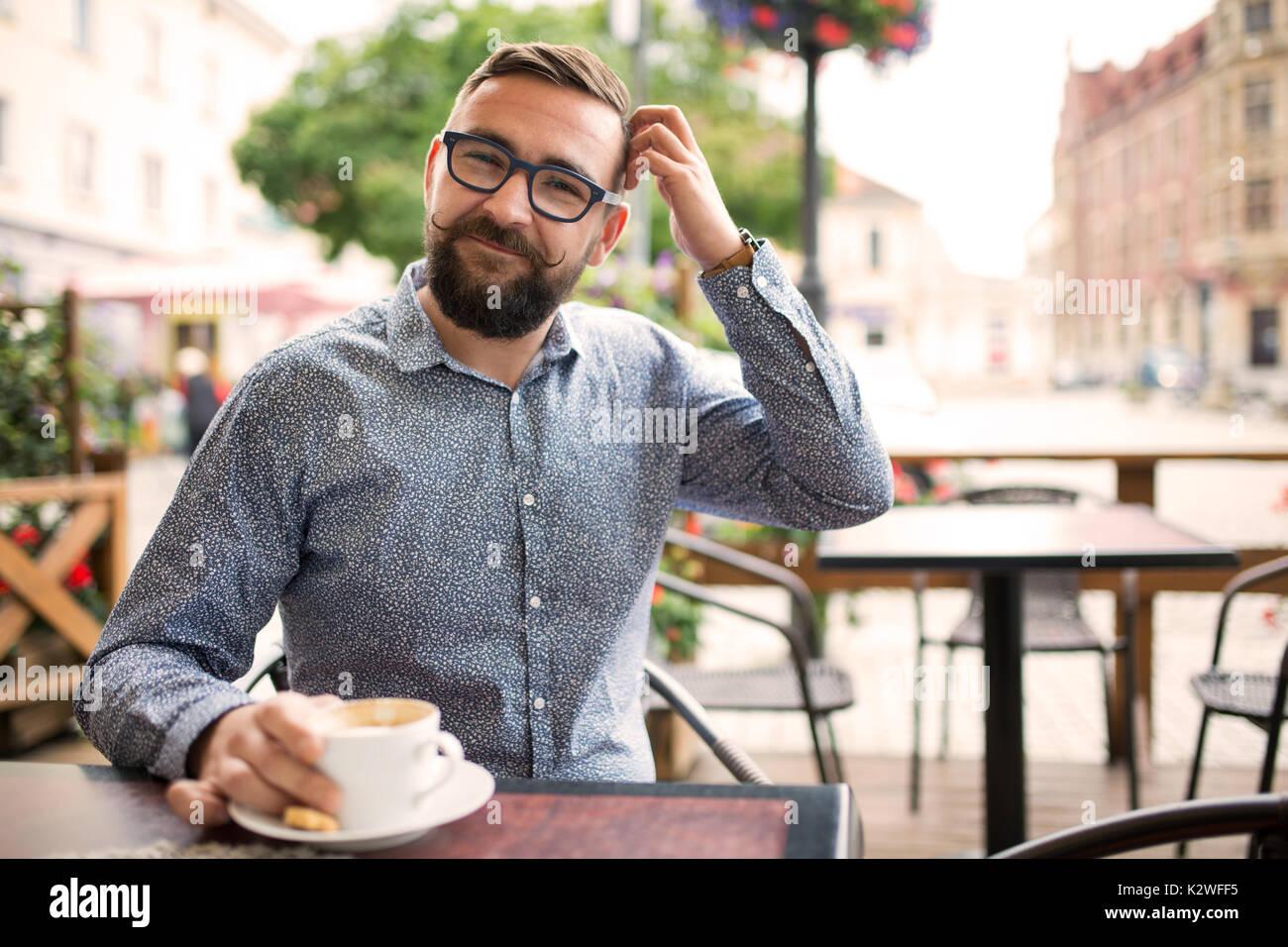 Beschämt lächelnd Mann in einem Cafe sitzen und den Kopf kratzen Stockbild
