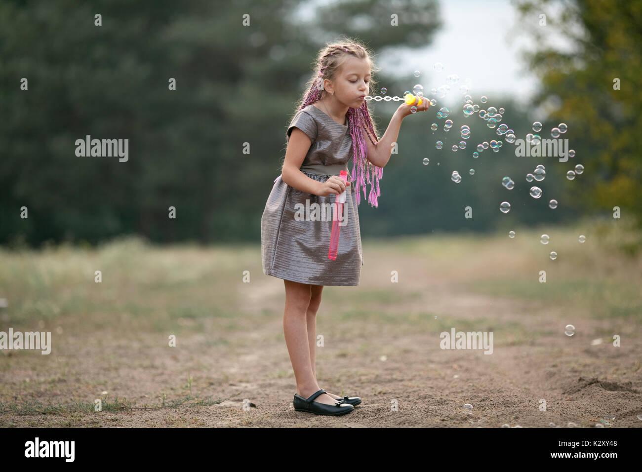 Glückliches Kind Mädchen mit Zöpfen bläst Seifenblasen auf Spaziergang im Park. Stockbild