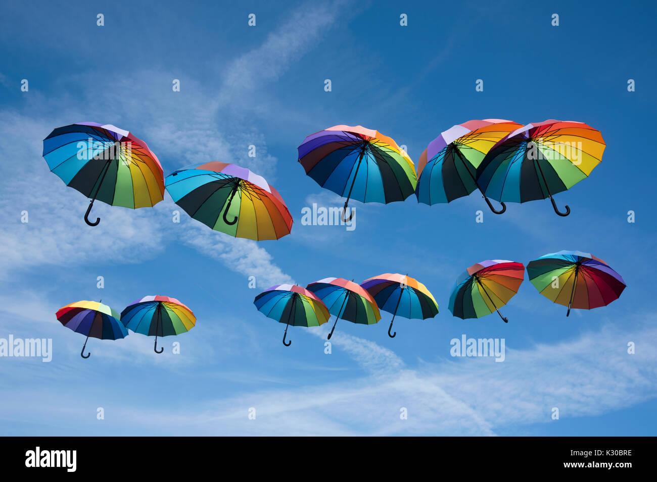 Regenbogenfarbenen Sonnenschirmen im Himmel schweben Stockbild