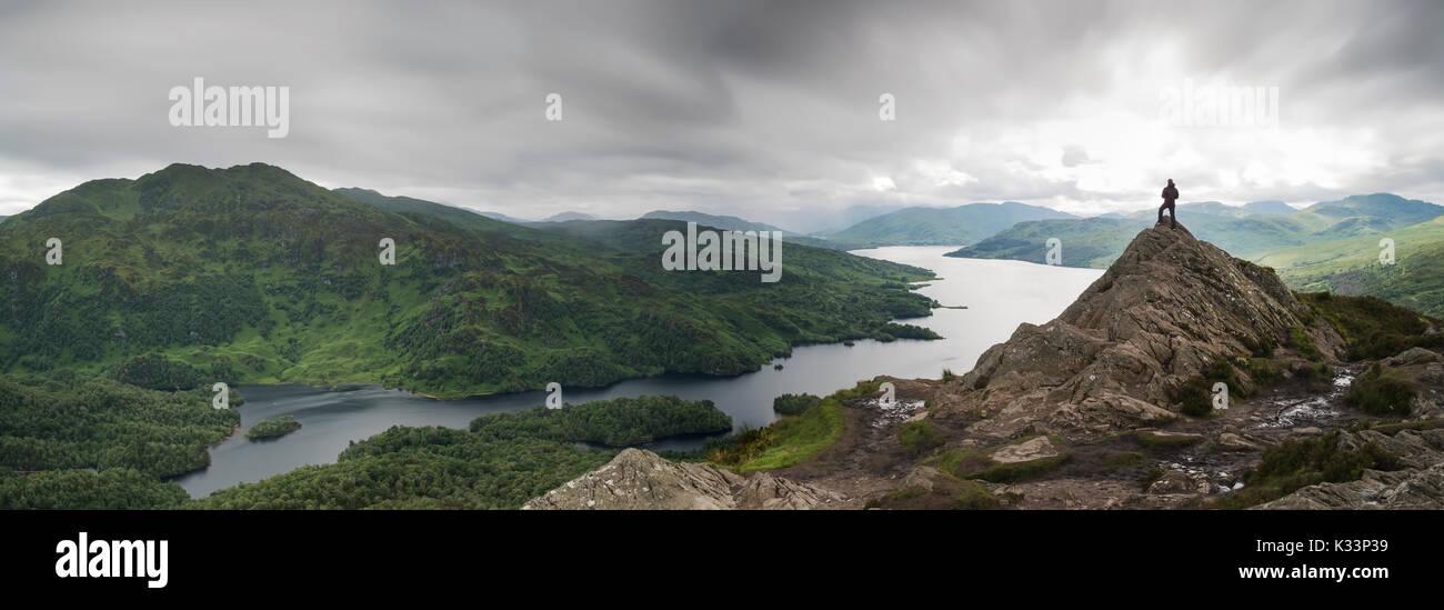 Ein Mann stand auf dem Gipfel des Ben A'an in den schottischen Highlands, Schottland. Vor der atemberaubenden Vista/view mit Wolken Hervorhebung der Abenteurer. Stockbild