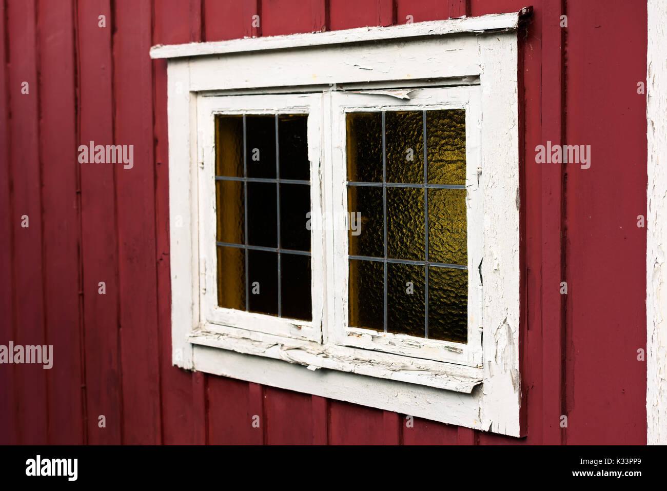 Alte Fenster auf einem roten Häuschen mit weissen Fensterrahmen. Der ...