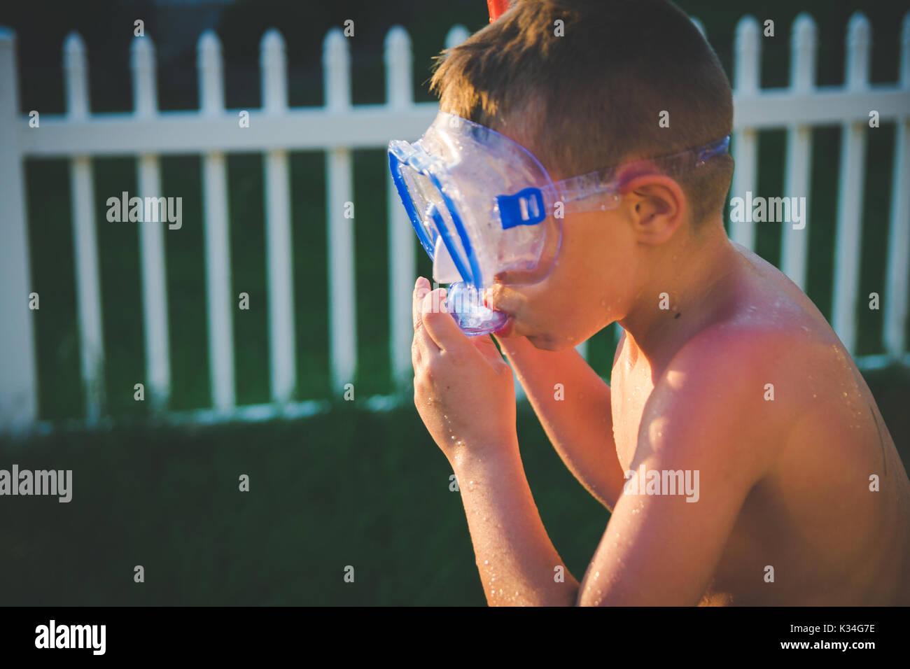 Ein Junge setzt auf einen Taucher mit Maske und Schnorchel im Sommer. Stockbild