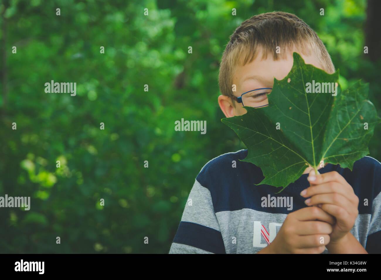 Ein kleiner Junge hält ein grünes Blatt vor seinem Gesicht. Stockbild