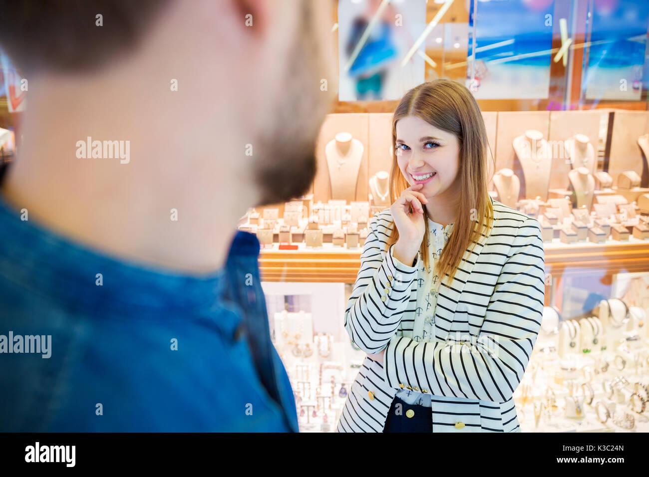 Ein Foto der jungen Frau, die auf mysteriöse Weise neben dem Schaufenster und lächelnd. Stockbild