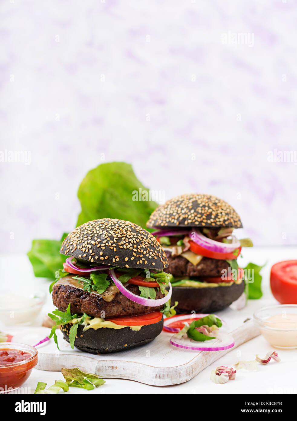 Schwarz big Sandwich - schwarz Hamburger mit saftigen Beef Burger, Käse, Tomaten und Zwiebel rot auf hellem Hintergrund. Stockbild