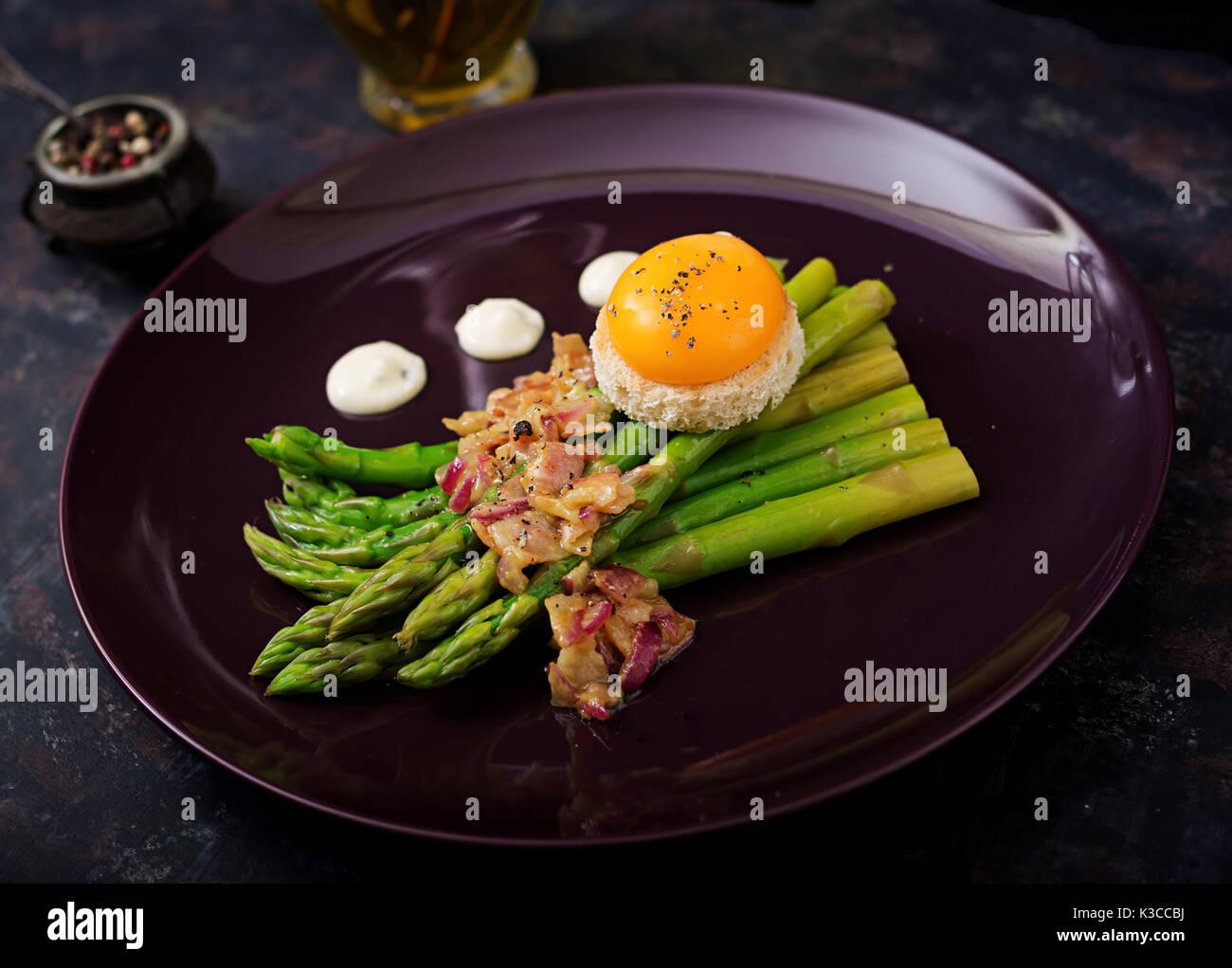 Junge Triebe von Spargel mit Schinken und Huhn Eigelb auf Toast Stockbild