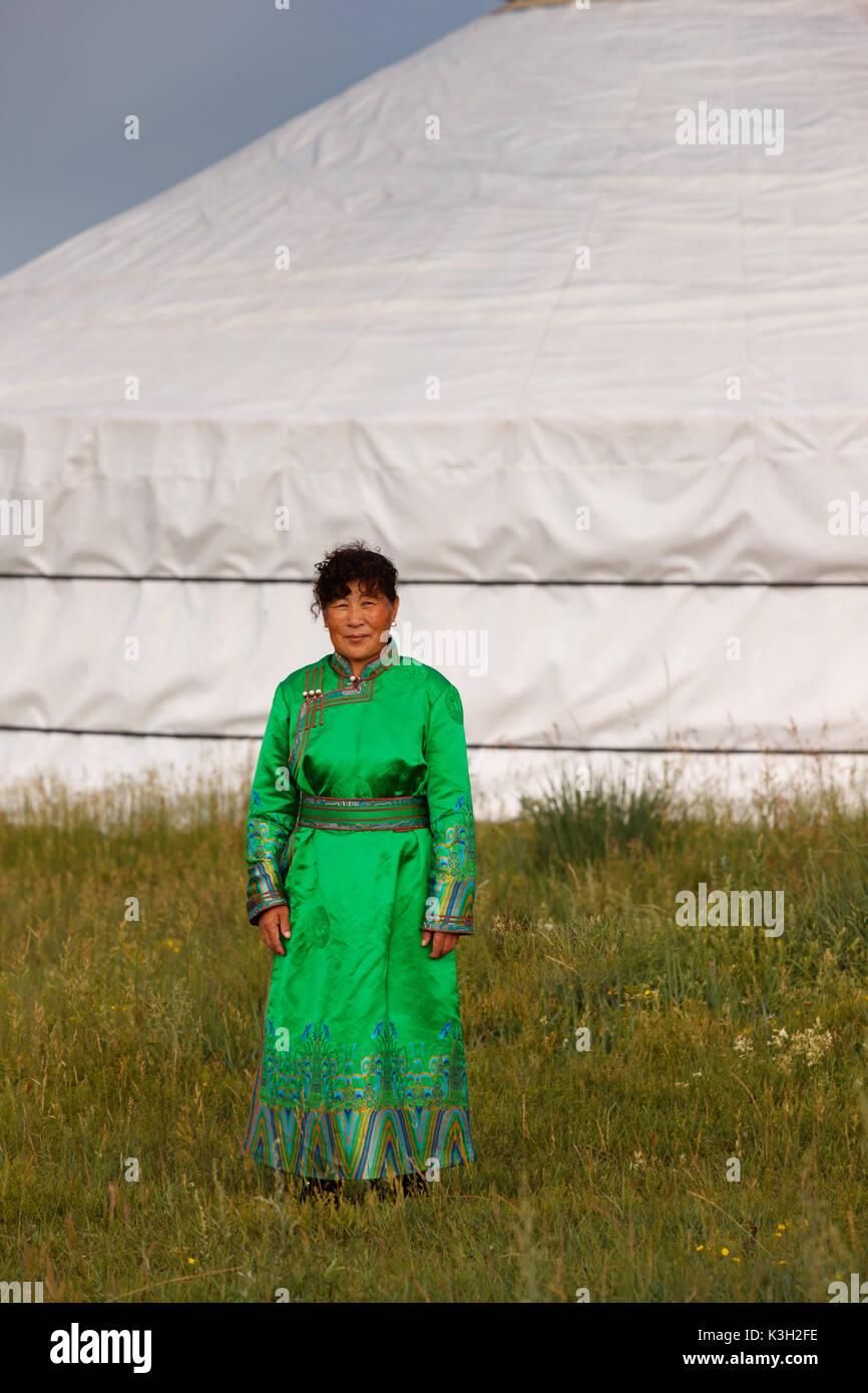 Die innere Mongolei, China-July 26, 2017: Unbekannter Mongolin mit ihrer traditionellen Kleidung vor ihrem Zelt (jurten) im Grünland. Stockbild