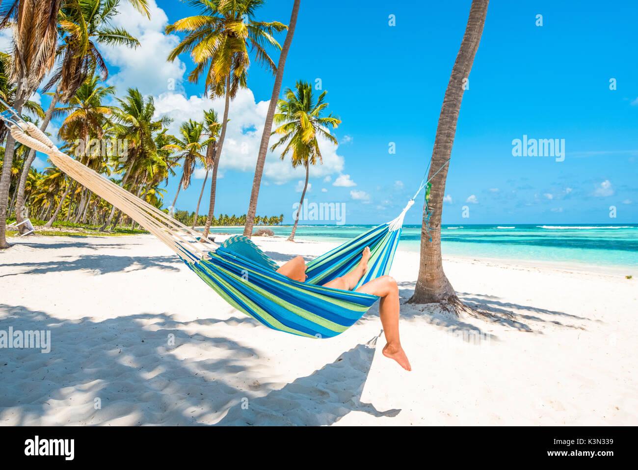 Canto de la Playa, Saona, East National Park (Parque Nacional del Este), Dominikanische Republik, Karibik. Frau entspannen auf einer Hängematte am Strand (MR). Stockbild