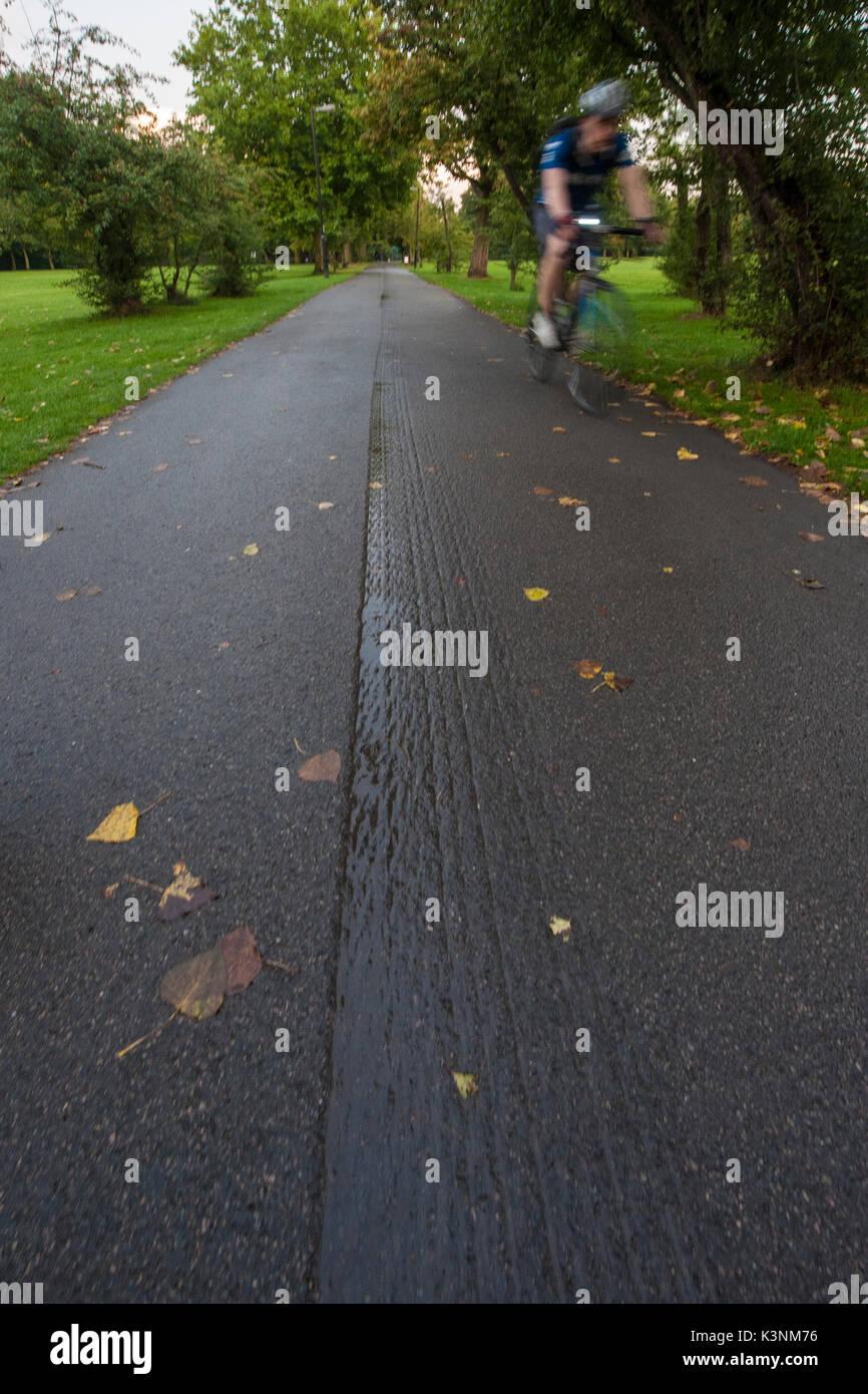 Ein Radfahrer Zyklen durch eine London Park Stockfoto