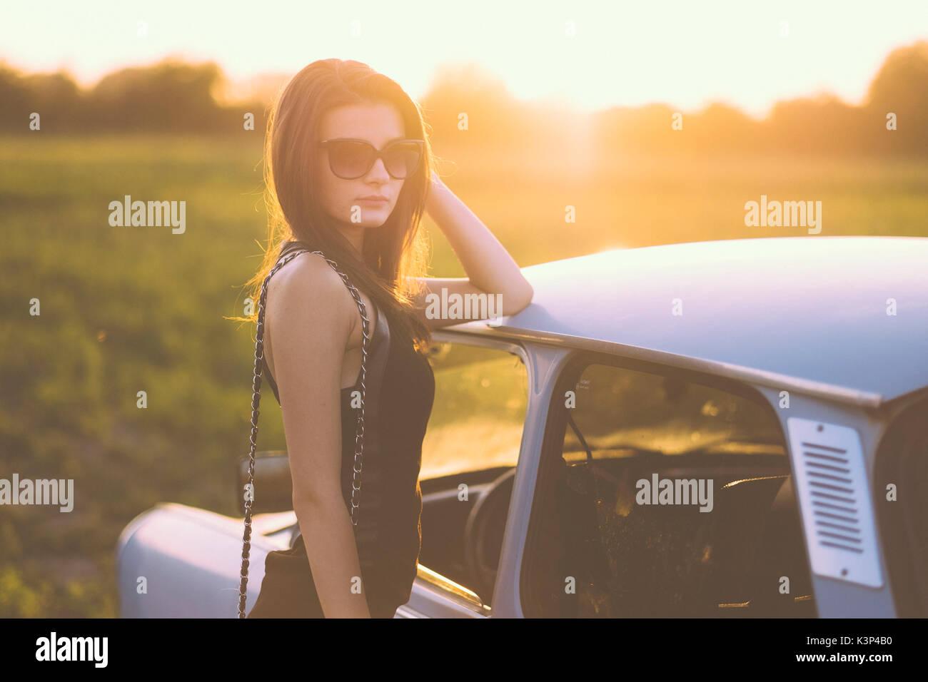 Frau mit einem retro Auto im Sommer Sonnenuntergang Stockfoto