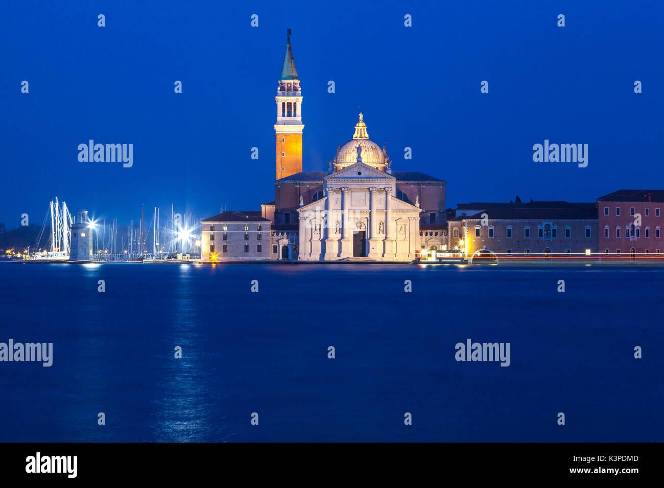 Venedig, Venetien, Italien, Blick auf die Insel San Giorgio Maggiore an der blauen Stunde mit Kirche und Kloster der Benediktiner beleuchtet und leichte Spuren von einem Stockfoto